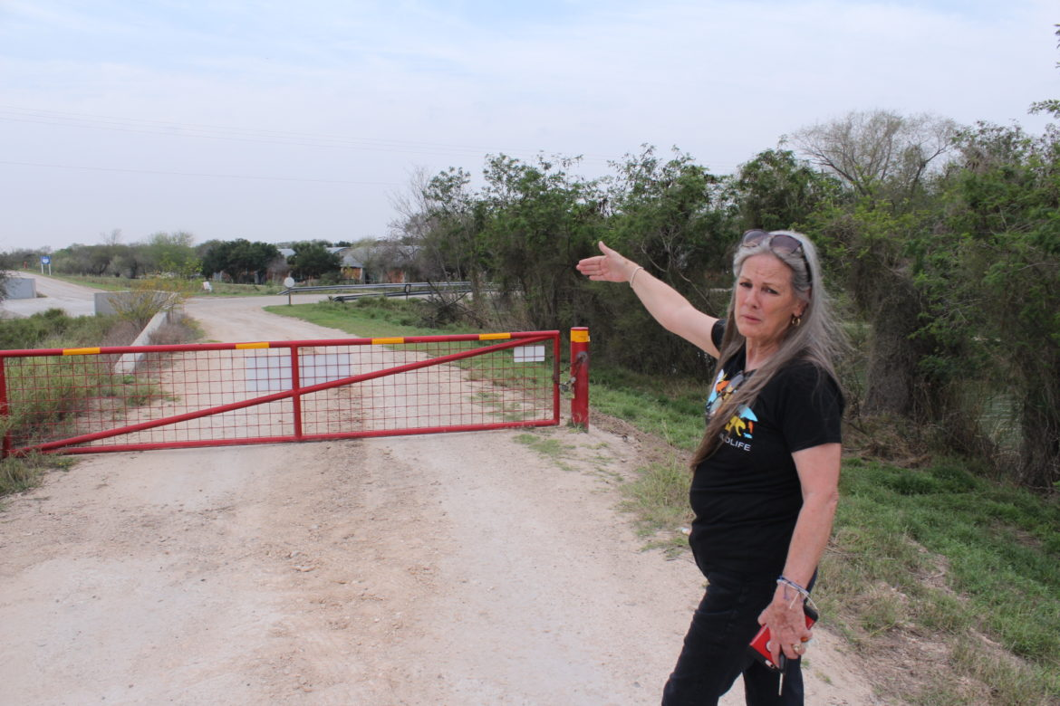 Defenders of Wildlife organizer Lorri Burnett points out a gate she says has been recently closed on the levee road near the National Butterfly Center.