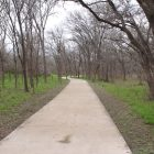 The concrete path that forms the main trail along Leon Creek at Pearsall Park.