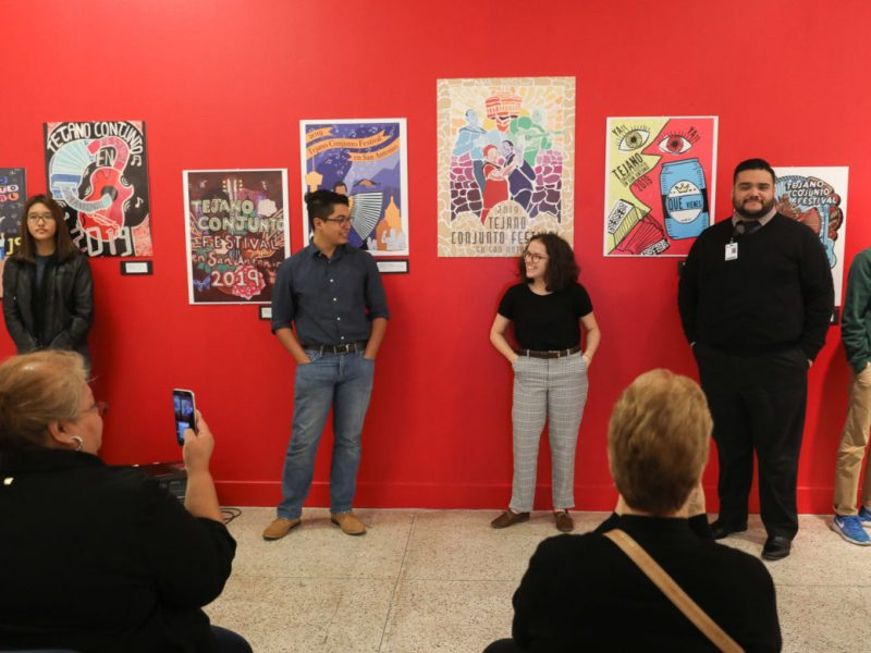 Artists stand in front of their winning entries for the poster design of the 2019 Tejano Conjunto Festival.