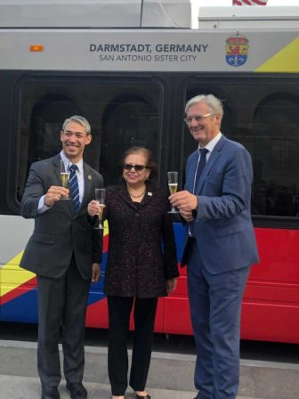"""(From left) Mayor Ron Nirenberg, VIA Board Chair Esperanza """"Hope"""" Andrade, and Lord Mayor of Darmstadt Jochen Partsch attend a dedication ceremony for a VIA Metropolitan Transit bus designed in honor of Darmstadt."""