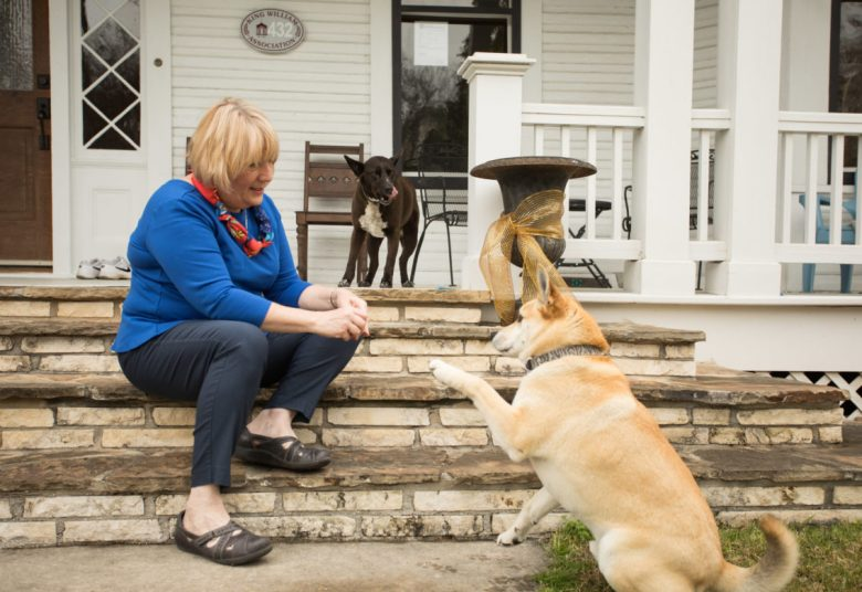 Shelley Galbraith gives treats to her rescue dogs Sandy and Tim on her front porch.