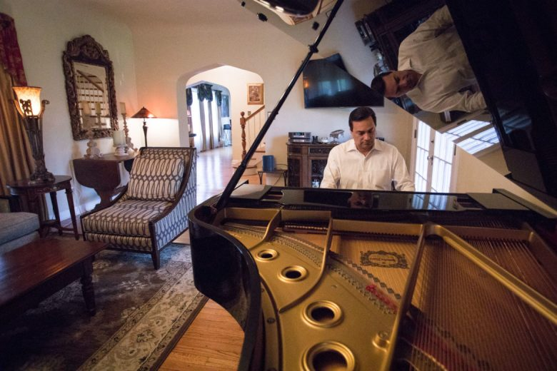 Mario Vazquez plays his piano in his home.