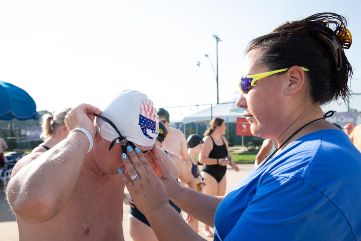 Special Olympics swimming coach Elizabeth Waugh helps a swimmer with his goggles.
