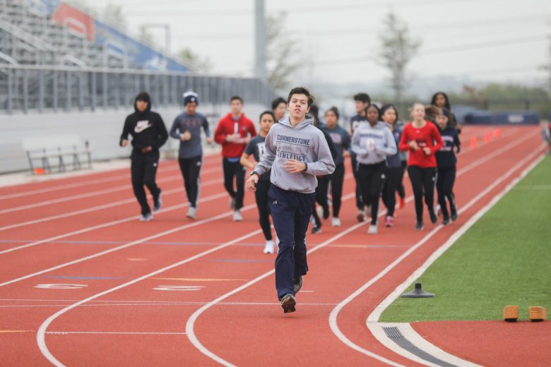 Students run on a track around the football field during physical education at Cornerstone.