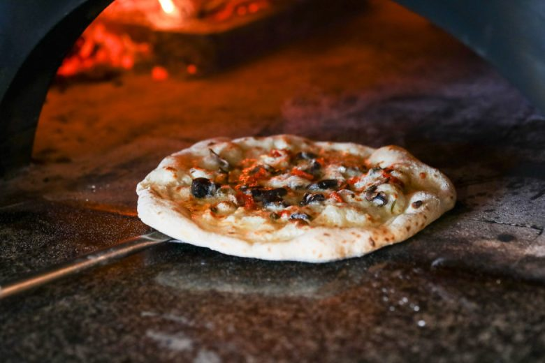 A freshly made pizza is pulled out of the wood burning oven.