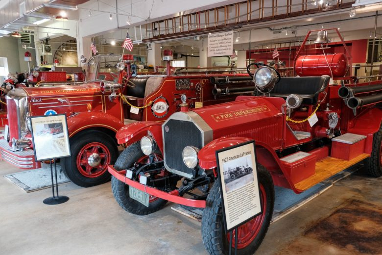 Vintage fire trucks line the front bays of the museum in the traditional bright red color.