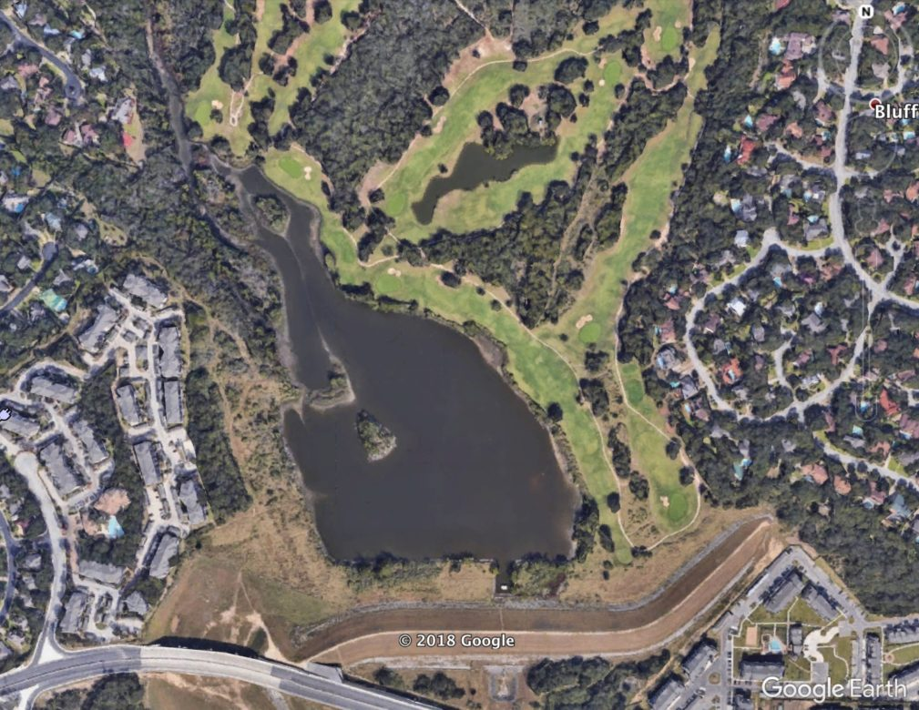 An aerial view of the dam, pond, and gold course.