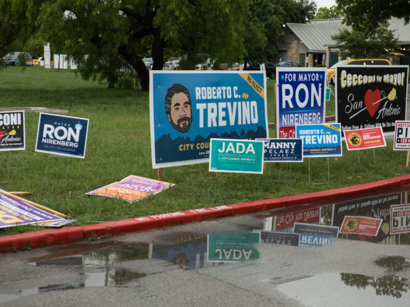 Signs line the entrance to Lion's Field on the third day of early voting on April 24, 2019.