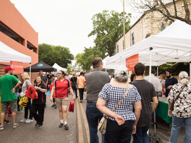 Festival-goers walk through the tents outside during the 7th annual San Antonio Book Festival.