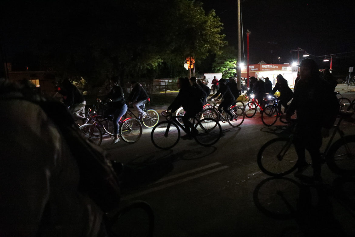 Friends of Tito Bradshaw ride their bicycles down Houston Street in his memory.