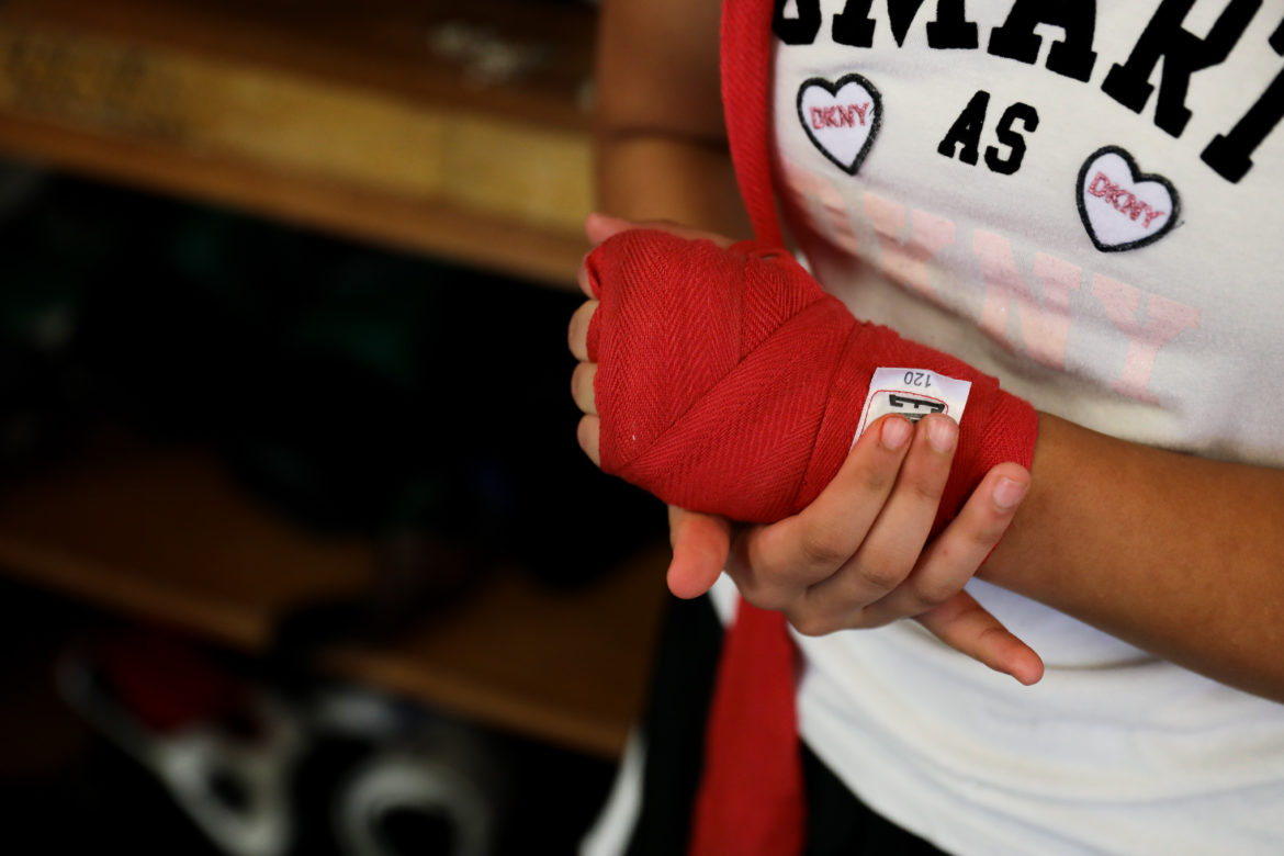 Students wrap their hands and wrists before gloves are put on.