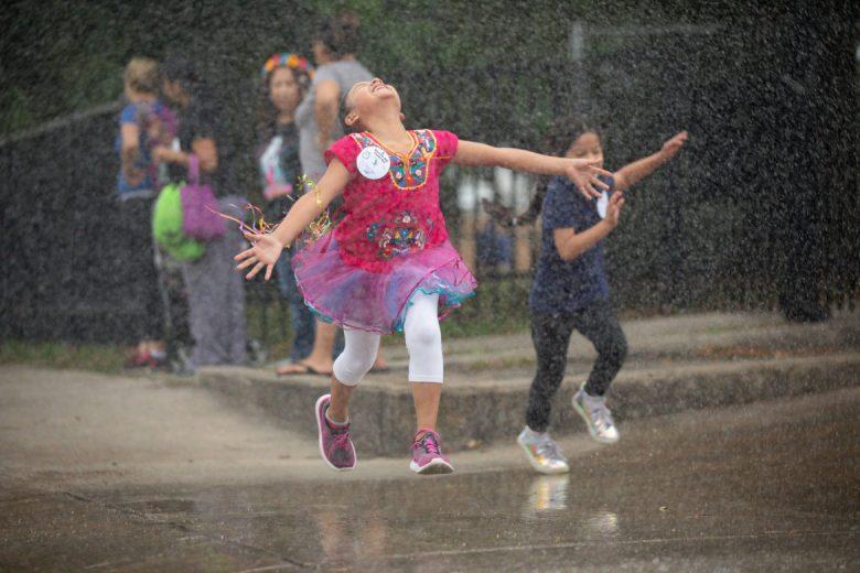 A child leaps through the rain during the Fiesta Run.