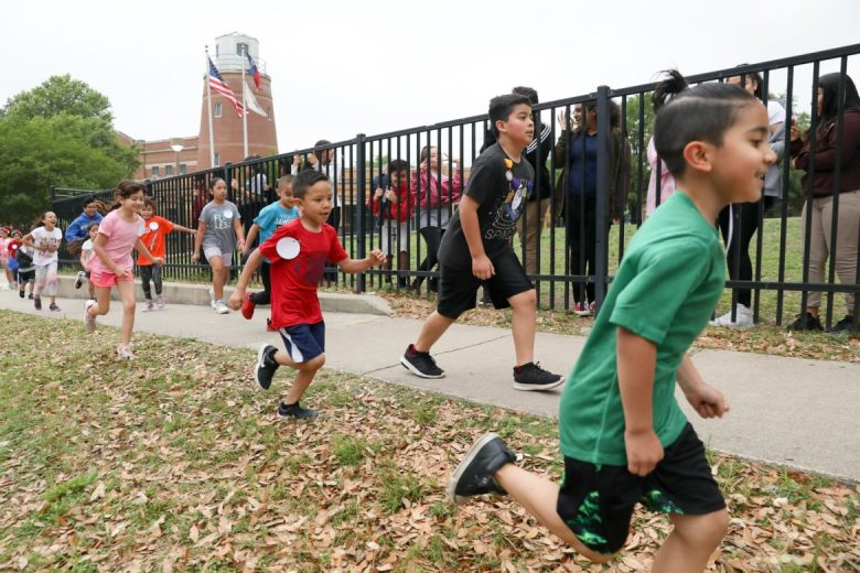 Beacon Hill Academy students run along the perimeter of the school during the Fiesta Run.