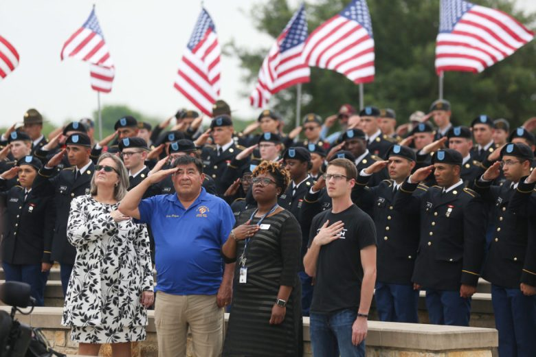 Attendees salute and hold their hands over their hearts as full honors were given to the 17 deceased veterans.