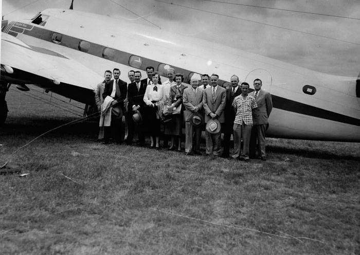 Tom Slick and friends stand in front of a plane in the 1950's.