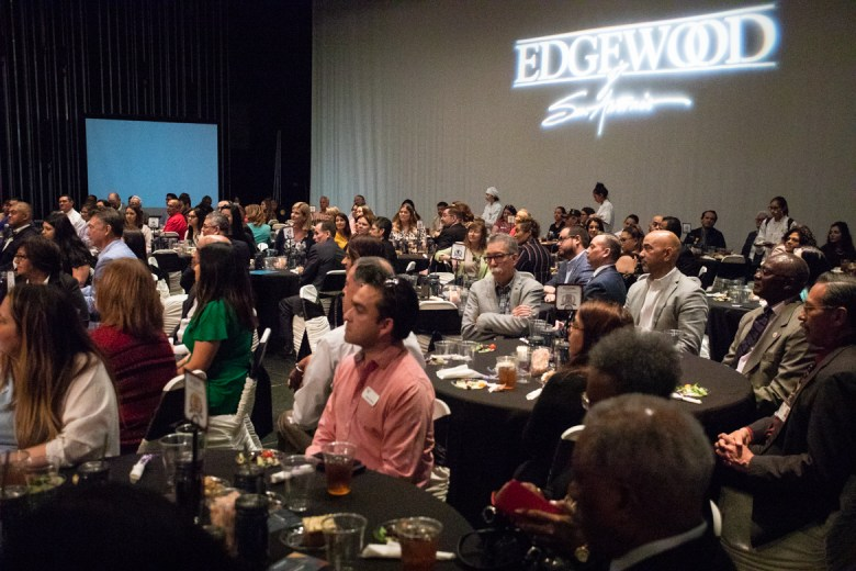 A large crowd sits on stage for the luncheon.