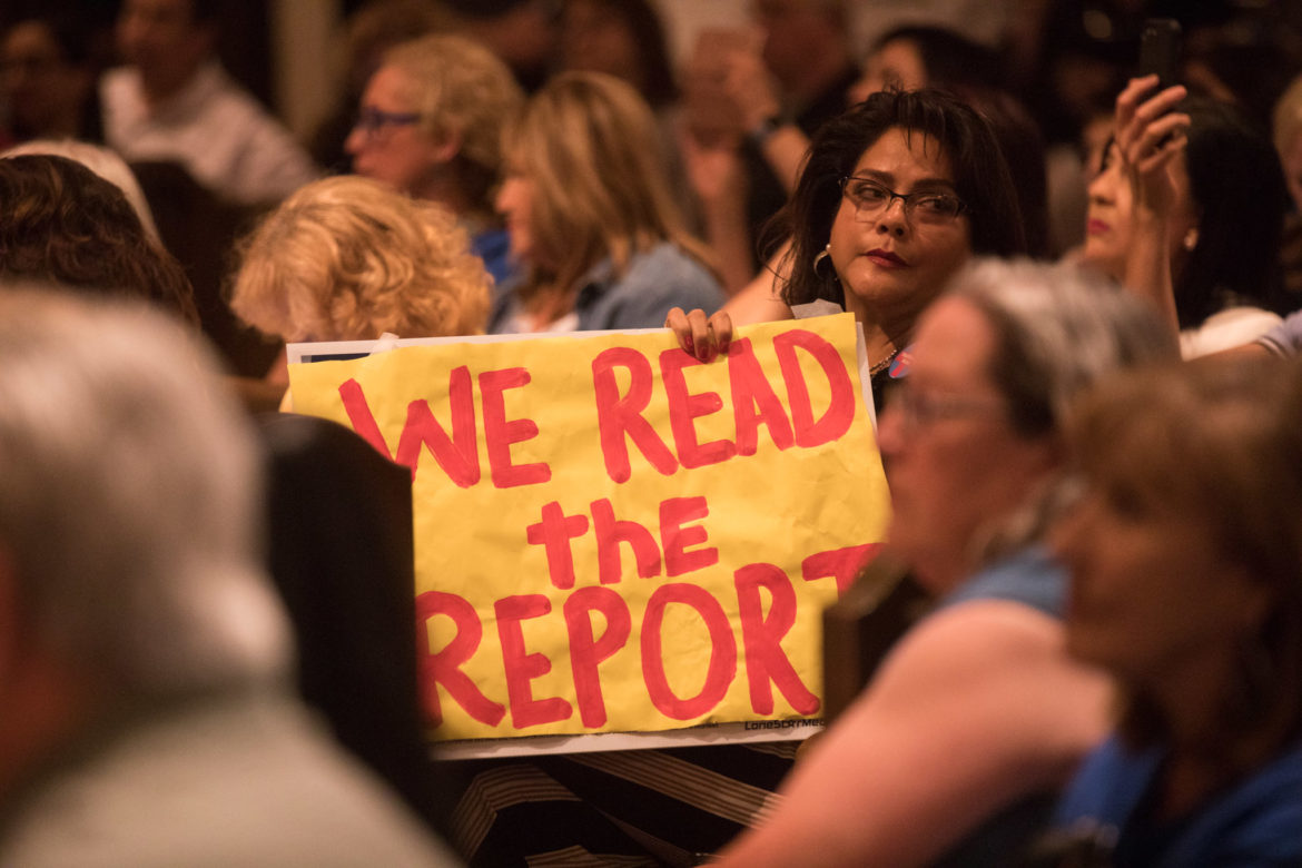 """Rosey Abuabara holds a sign that reads """"We read the report."""""""