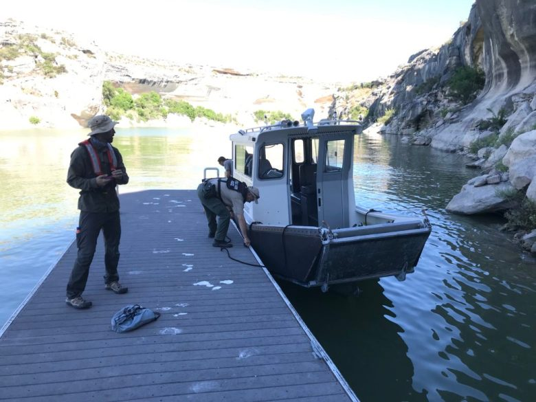 Visitors to Panther Cave tie a boat to the floating dock that forms the only access point for the rock art mural.