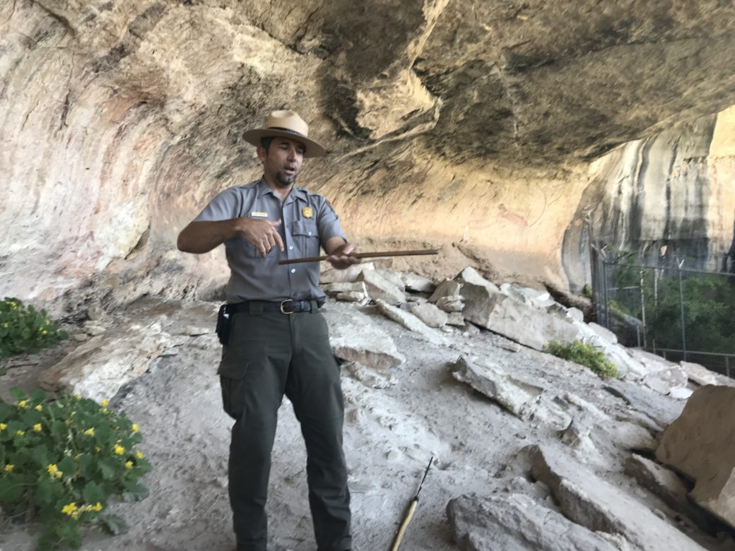 Jack Johnson, park archaeologist for Amistad National Recreation Area, demonstrates the use of a rabbit stick, a primitive weapon likely depicted on the walls of Panther Cave.