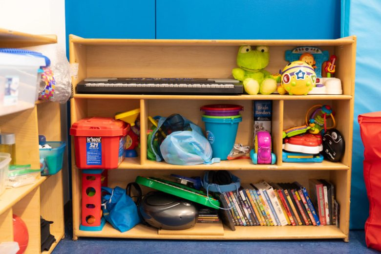Musical instruments, books, and colorful toys line the shelves of a classroom at the Autism Treatment Center.