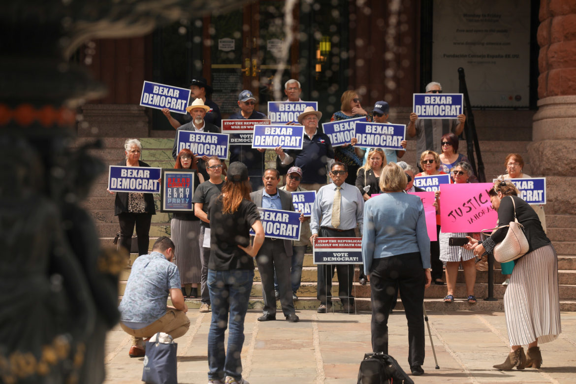 Members of the Bexar County Democratic Party assemble on the front steps of the Bexar County Courthouse.