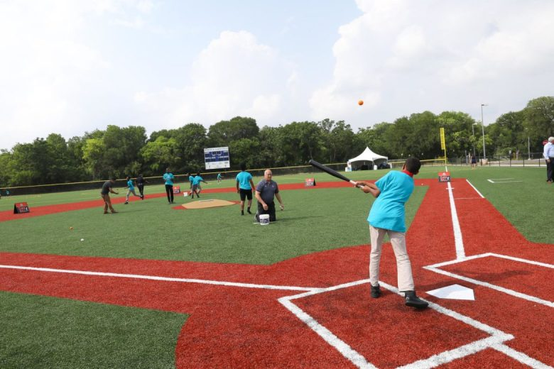 A pitch thrown by Cal Ripken Jr. is hit towards the outfield at the new Harvey Najim Baseball Field at the Boys & Girls Club in the Eastside.