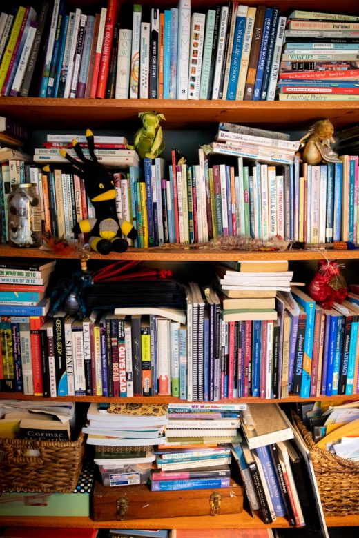 A large bookcase filled with writing book make subtle bows in the shelves.