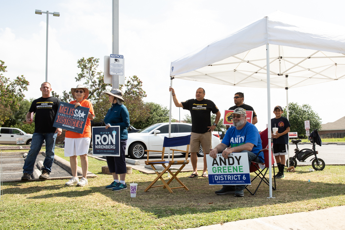Campaign supporters and volunteers hold up signs in front of Great Northwest Library on election day.