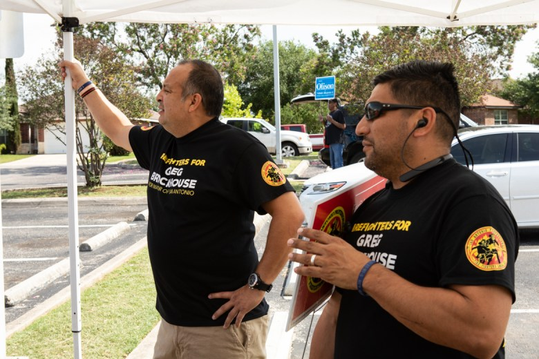 """(From left) Firefighters Roland Aguirre and Rene """"Bug"""" Guerra answer questions on behalf of the Firefighter's Union in front of the Great Northwest Library."""