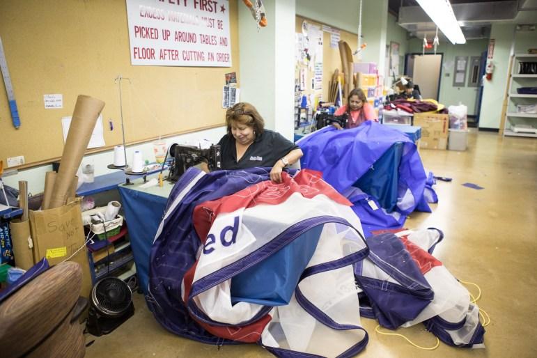 Estella Delgado, seamstress, works on a school flag.