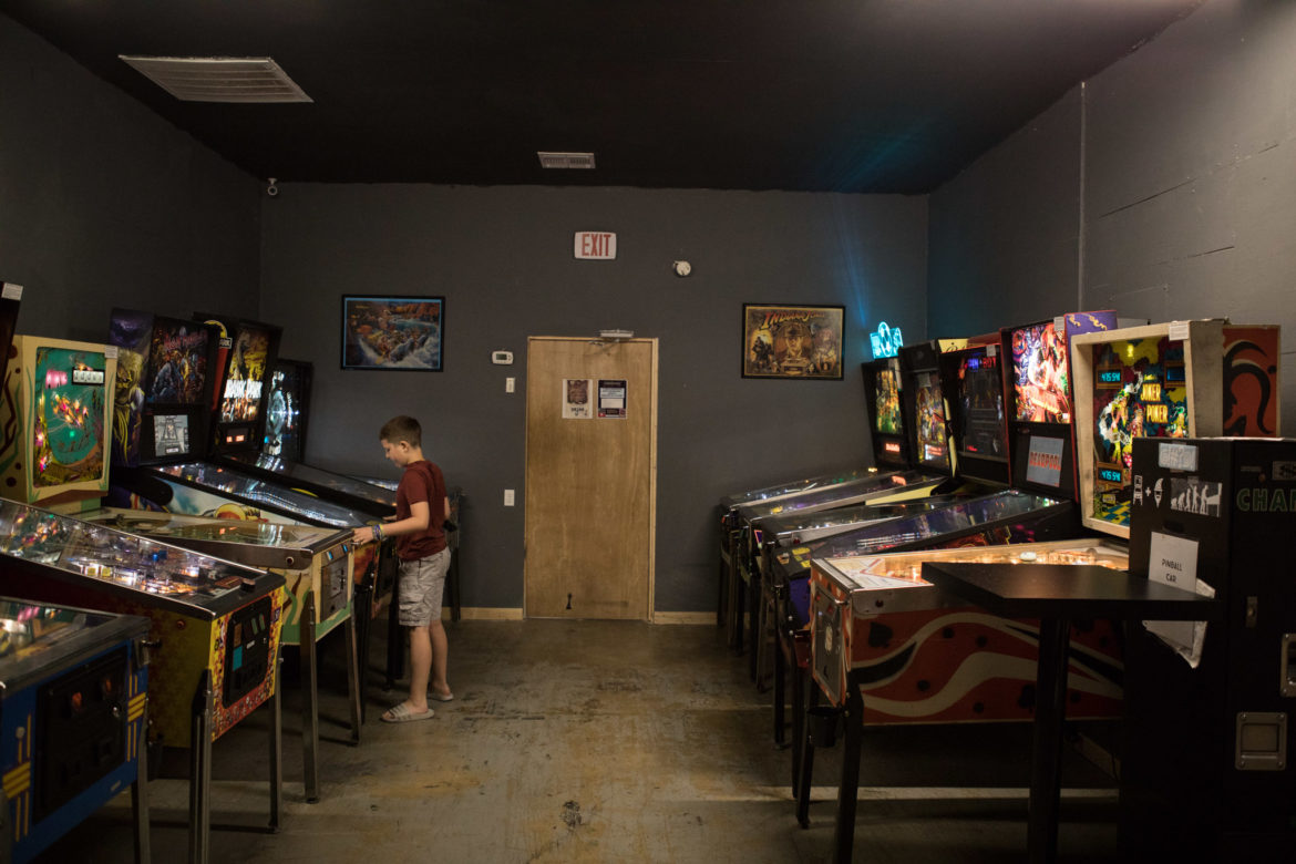 A boy plays pinball in the back room.