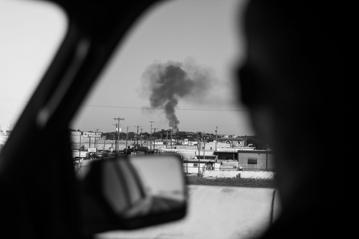 A large cloud of black smoke from a fire is seen from a distance as Mayor Nirenberg travels to an event.