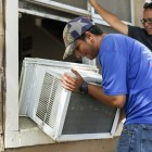 Thomas Jimenez of Temp Tex removes a dated air conditioning unit at a San Antonio Housing Authority complex home.