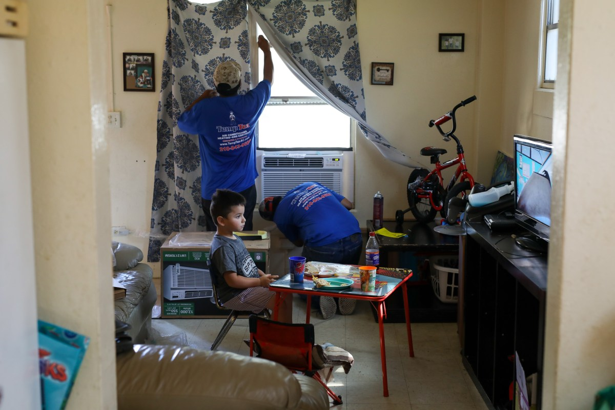 Dominic Trejo, 4, watches television in his home as Thomas Jimenez and Henry Vasquez install a new air conditioning window unit in the living room.