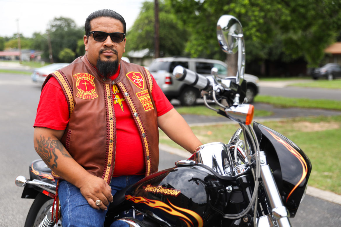 Albert Gonzales sits atop one of his motorcycles outside the church he leads in sermon.