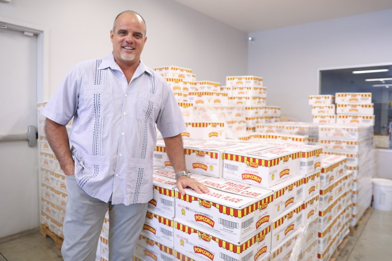 Ricos CEO Tony Liberto stands in front of a large shipment of Ricos Popcorn.