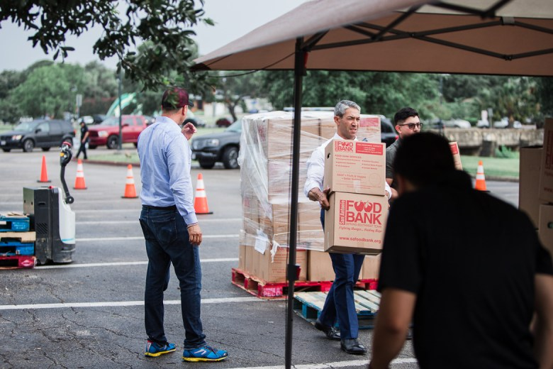 Mayor Ron Nirenberg helps load boxes of food from the San Antonio food bank to storm victims vehicles on June 11, 2019.