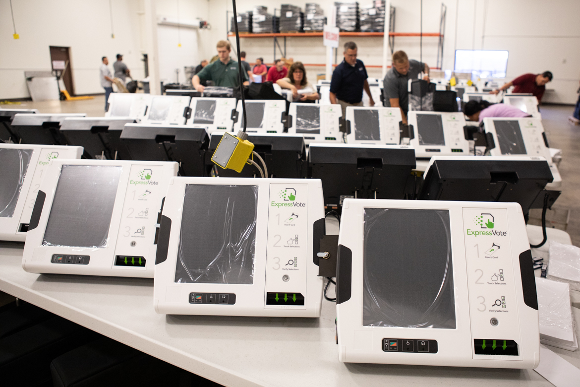New voting machines are unpacked for inspection before being shelved.