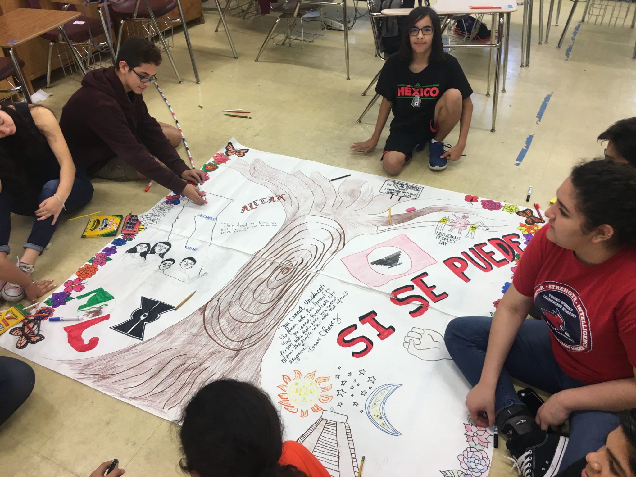 Students draw the history of Mexican Americans in a mural, with a large tree at the center.