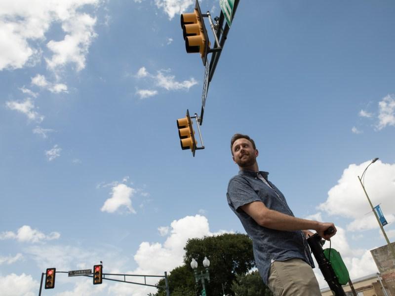 Senior Reporter Brendan Gibbons rides a scooter in downtown San Antonio.