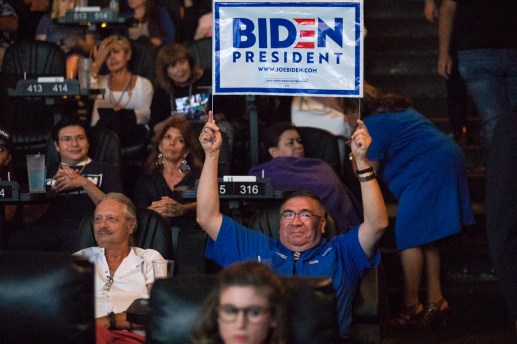 Lawrence Romo holds up a sign supporting Joe Biden.