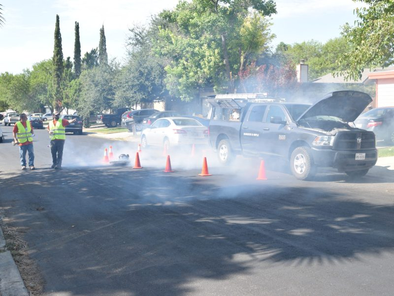 Cews with San Antonio Water System contractor Burgess and Niple blow smoke into a sewer main on Spring Club Drive.