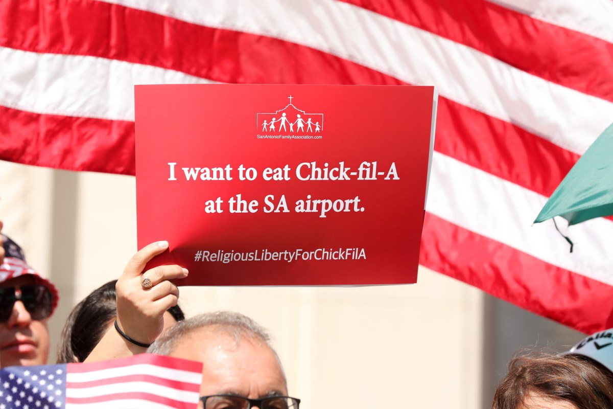 People hold up signs in support of Chick-fil-A and religious liberty during a 2019 event.