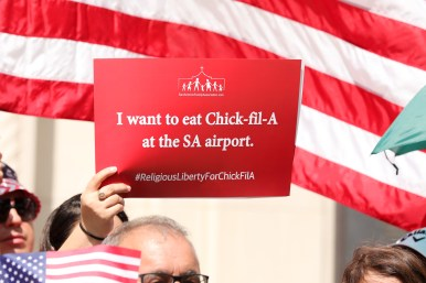 Attendees hold up signs in support of Chick-fil-A and religious liberty.