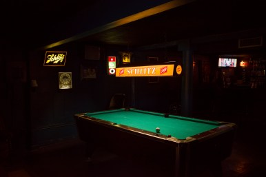A dimly lit pool table invites patrons to play a game with a drink.