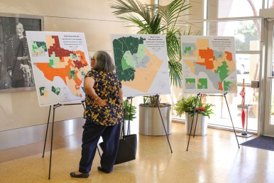 A hearing attendee inspects the Texas Congressional District map posted outside the meeting conference room.