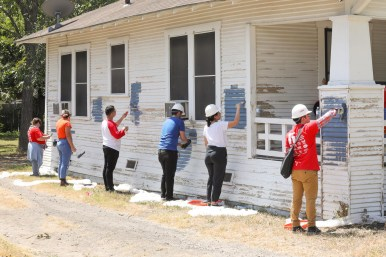 Evenly spaced volunteers repaint a house.
