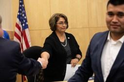 Elda Flores shakes hands after handing in her resignation.