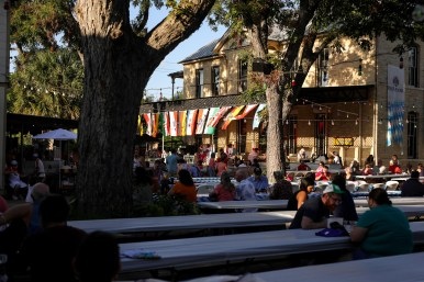 Attendees sit at long German-style beer garden tables and enjoy cold beer and hot food.
