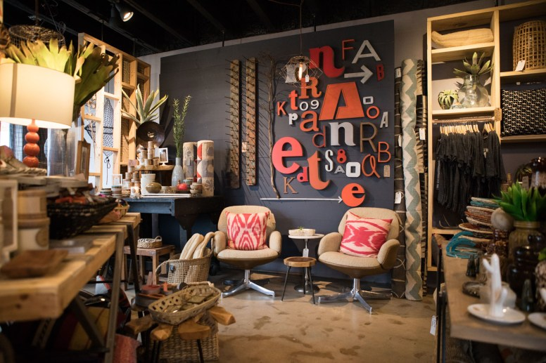 Vintage lettering forms a backdrop for a pair of chairs and other items for sale.